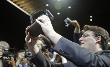 FILE - In this June 11, 2015 file photo, Oculus founder Palmer Luckey holds up the new Oculus Rift virtual reality headset for photographers following a news conference, in San Francisco. While more than 1,500 attendees are expected on Saturday, Aug. 29, 2015, at the VRLA expo, the event probably won't feel very crowded. That's because headset-wearing convention goers will be transported to other worlds during the second-annual celebration of virtual reality at the Los Angeles Convention Center. (AP Photo/Eric Risberg, File)