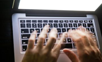 Typing fast late at night. Motion blur on hands for effect. Long exposure.