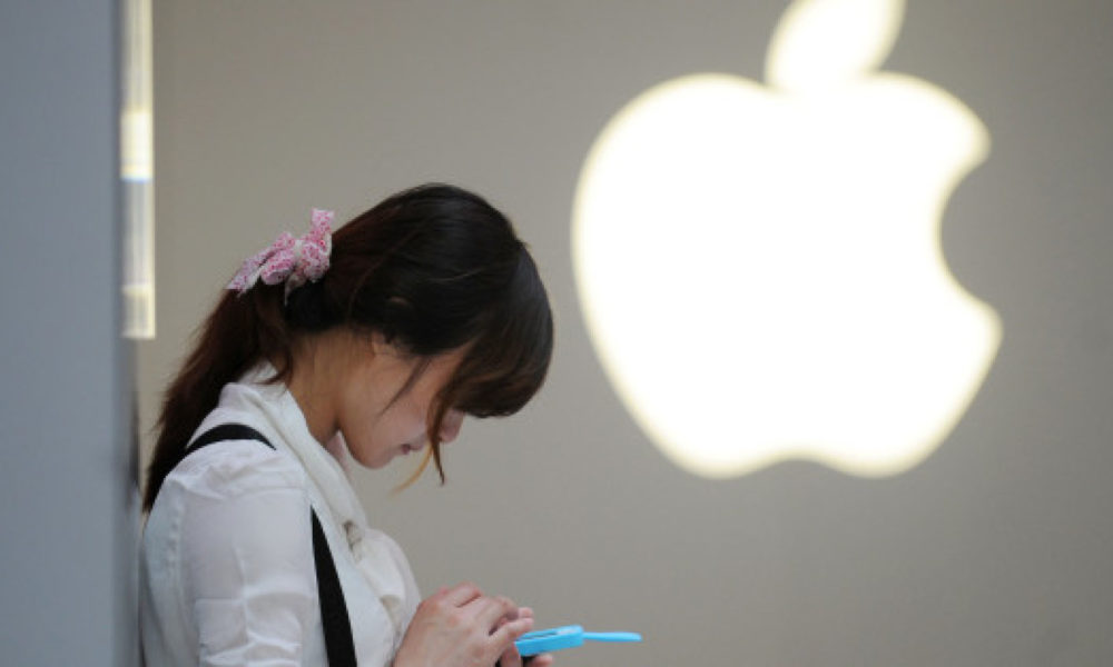 A woman uses her mobile phone outside an Apple store in Shanghai on May 7, 2012. A Chinese computer company which sued Apple over the rights to the iPad trademark in China is now in talks for an out-of-court settlement, a lawyer for the firm said on May 7.  AFP PHOTO/Peter PARKS        (Photo credit should read PETER PARKS/AFP/Getty Images)