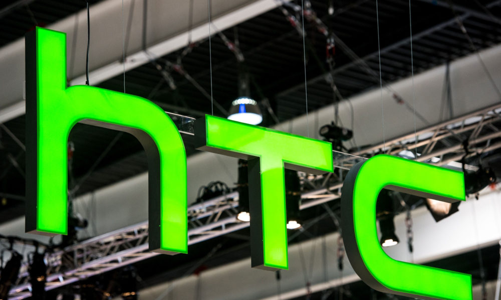 A HTC logo hangs from a beam during the Mobile World Congress on the third day of the MWC in Barcelona, on March 1, 2017.  Phone makers will seek to seduce new buyers with artificial intelligence functions and other innovations at the world's biggest mobile fair starting today in Spain. / AFP PHOTO / Josep LAGO        (Photo credit should read JOSEP LAGO/AFP/Getty Images)