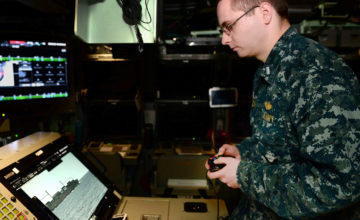 In this Feb. 2, 2018 photo released by the U.S. Navy, Lt. j.g. William Gregory uses an Xbox game controller to maneuver the photonics mast aboard the submarine scheduled to be commissioned as the USS Colorado on Saturday, March 17, 2018, in Groton, Conn. (Steven Hoskins/U.S. Navy via AP)